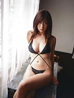 Busty asian babe showing off her delectable body in a bikini