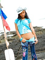 Tiny Asian girl is by the beach and strips out of her jeans to show her tight body