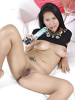Busty Thai beauty shoving a big sex toy into her tight hairy pussy