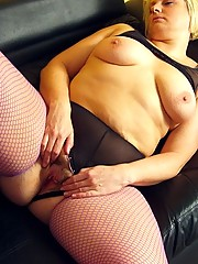 Curvy blonde housewife in purple fishnet thigh highs