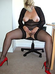 Busty secretary in black stockings and red heels