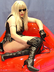 Slutty tranny with whip sitting on blow up red lips