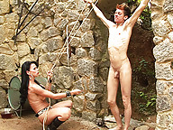 Shemale dominatrix at work in her dungeon