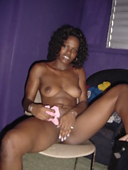 Curly-haired black chick strips naked and spreads her legs