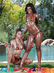 Out in the hot summer sun Angel Cummings and Mariah Kakes are greased up good. These two black beauties don